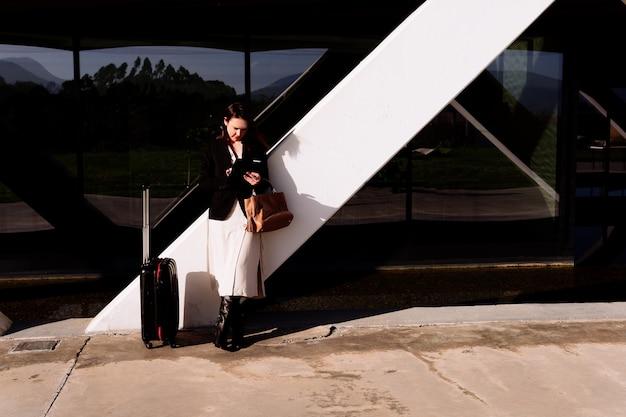 Красивая молодая взрослая женщина в деловой поездке, вызывая такси в аэропорт или проверяя электронную почту в деловой зоне или индустриальном парке, перевозя чемодан. бизнес-концепция