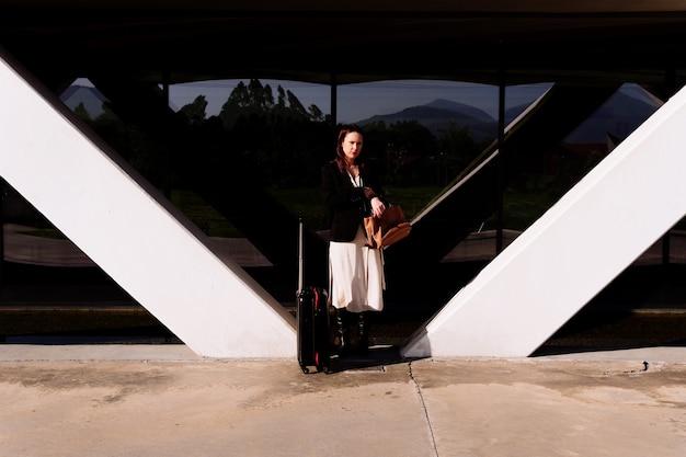 Красивая молодая взрослая женщина в деловой поездке задумчиво на улице деловым районом или индустриальным парком, перевозя чемодан. концепция делового путешествия
