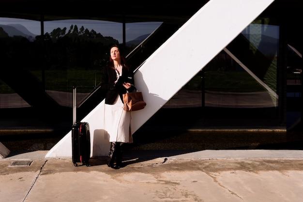 Красивая молодая взрослая женщина в деловой поездке, задумчивой на улице, проверяя электронную почту бизнес-зоной или индустриальным парком, перевозя чемодан. концепция делового путешествия