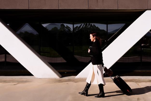 Красивая молодая взрослая женщина в деловой поездке, идущей через деловой район или индустриальный парк, перевозя чемодан. бизнес-концепция