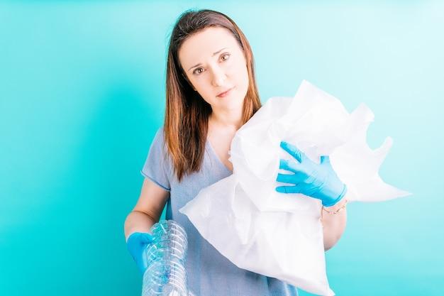 青い背景にペットボトルをリサイクルする美しい若い大人の女性。リサイクルの概念。プラスチックフリー