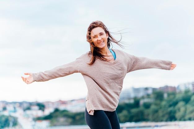 Красивая молодая взрослая женщина с распростертыми объятиями, улыбаясь с чувством свободы
