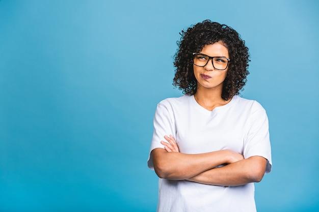 질문, 잠겨있는 식에 대해 생각하는 입술에 손으로 고립 된 파란색 배경 위에 아름 다운 젊은 아프리카 계 미국인 비즈니스 여자. 사려 깊은 얼굴로 웃고. 의심 개념.