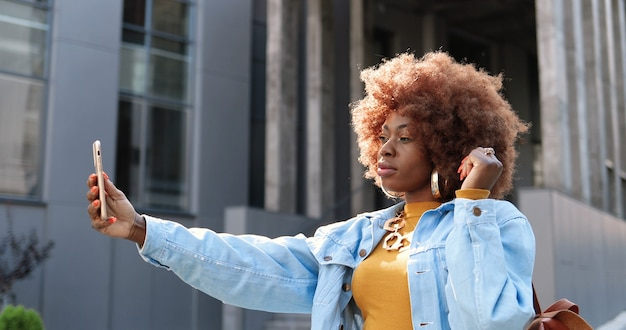 通りでselfie写真を撮っている間スマートフォンのカメラにポーズをとって美しい若いアフリカ系アメリカ人の巻き毛の女性。携帯電話で自分撮り写真を作るかなりスタイリッシュなクールな女性。