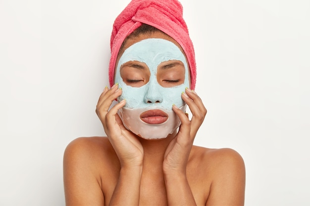 Beautiful young african american woman applies facial clay mask on face, touches skin gently, keeps eyes closed, wears wrapped towel on head, stands with bare shoulders, makes beauty treatments