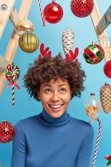 Beautiful young african american woman with curly hair looks above smiles gladfully dressed in casual poloneck surrounded by new year toys