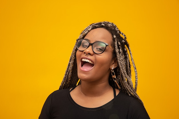 Beautiful young african american woman with dread hair and eyeglasses on yellow