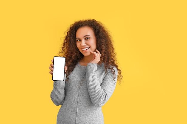Красивая молодая афро-американская женщина с мобильным телефоном на цветном фоне