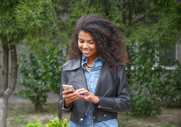 Красивая молодая афро-американская женщина с мобильным телефоном на открытом воздухе