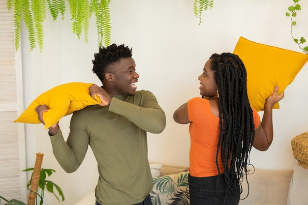 Beautiful young african couple pillow fight