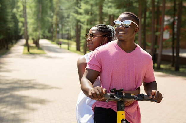 Beautiful young african couple riding in summer on electrical sink