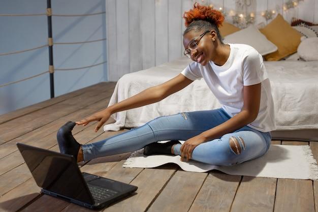 Красивая молодая африканская женщина занимается спортом дома перед ноутбуком