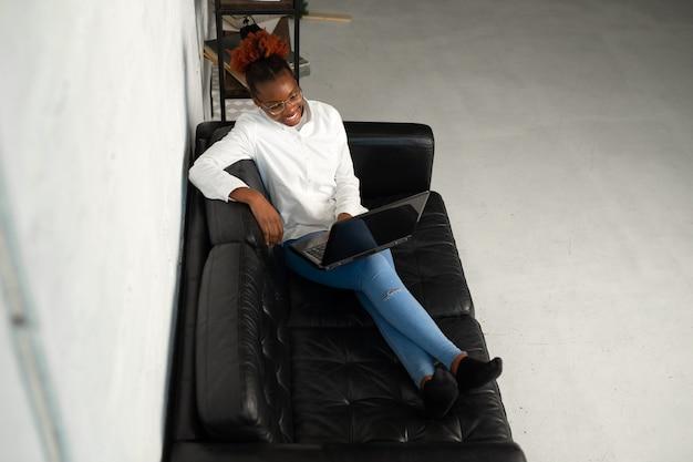 ラップトップと白いシャツを着た美しい若いアフリカの女性は黒いソファに座っています
