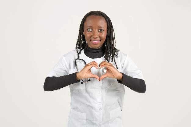 手ジェスチャーで医療服を着た美しい若いアフリカの女性
