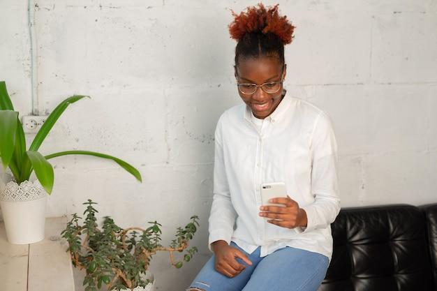 携帯電話と白いシャツの美しい若いアフリカの女性