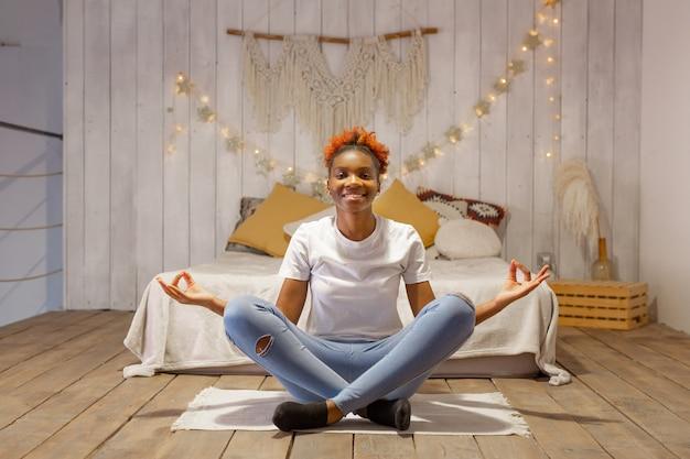 Красивая молодая африканская женщина в позе йоги дома в спальне