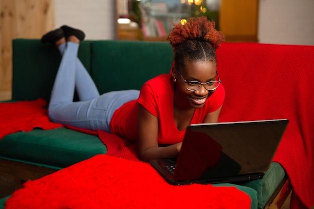 美しい若いアフリカの女性はソファの上にラップトップで横たわっています