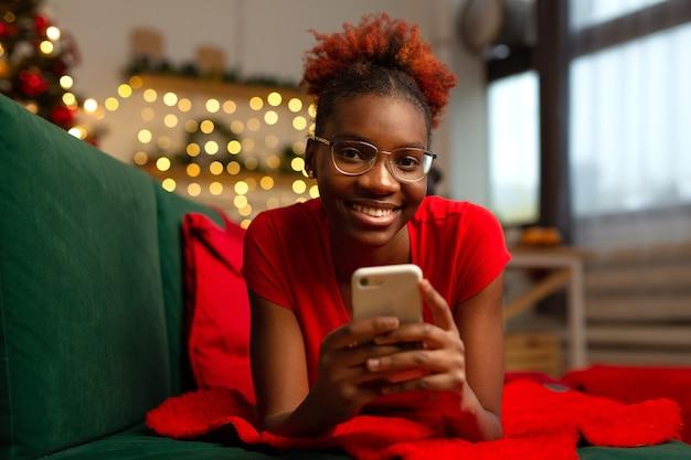 美しい若いアフリカの女性はソファの上に携帯電話で横たわっています