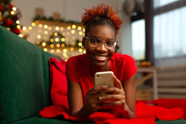 Beautiful young african female lies with a mobile phone on the couch