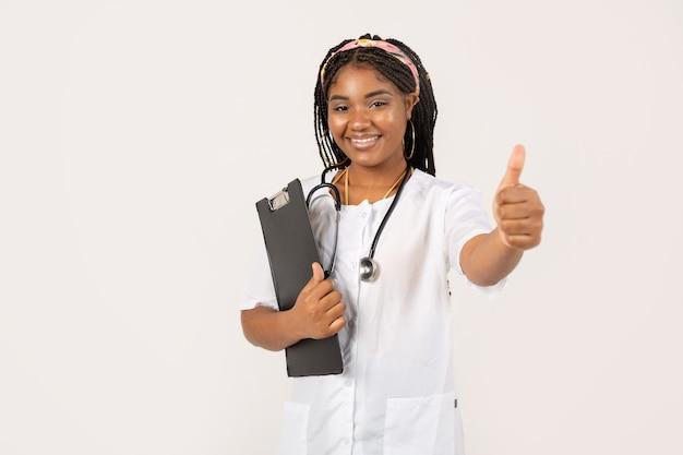 手のジェスチャーで医療用ガウンの白い背景の上の美しい若いアフリカの女性