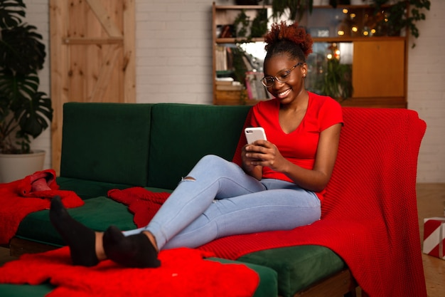 Beautiful young african female sitting with mobile phone on the sofa