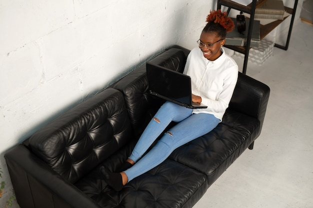 Beautiful young african female in a white shirt with a laptop sits on a black sofa