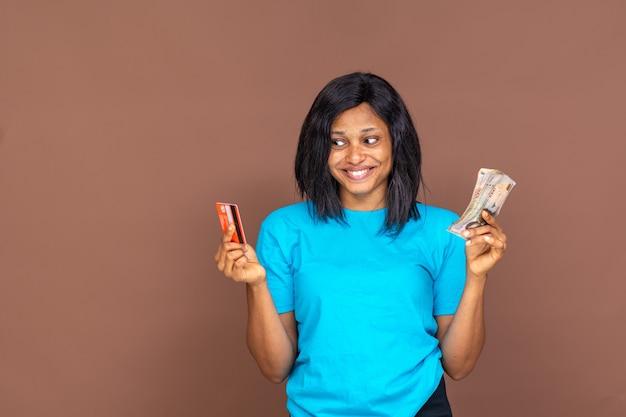 한 손에는 신용카드를, 다른 한 손에는 현금을 들고 있는 아름다운 젊은 아프리카 여성이 어느 것을 사용할지 결정하려고 합니다.