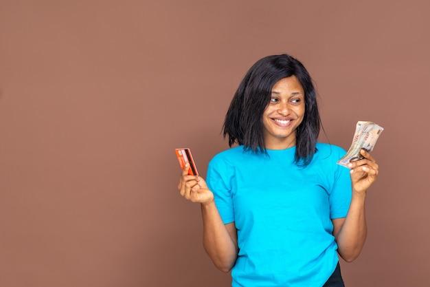 한 손에는 신용카드를, 다른 한 손에는 현금을 들고 있는 아름다운 아프리카 여성이 지불 옵션을 결정하려고 합니다.