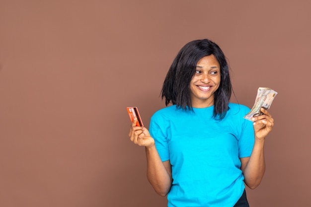Beautiful young african lady holding a credit card on one hand and cash in the other, trying to decide her payment option