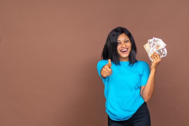 한 손에는 돈을 들고 다른 손에는 엄지손가락을 치켜드는 아름다운 젊은 아프리카 여성이 행복해 보이는 얼굴에 미소를 띠고 있다