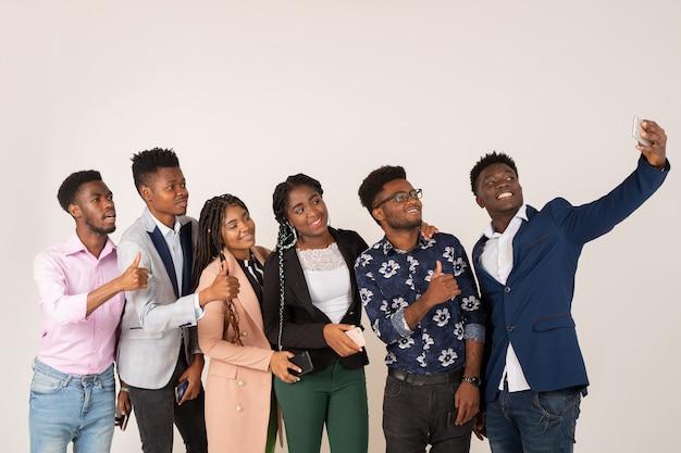 Красивые молодые африканцы на белом фоне фотографируются по телефону