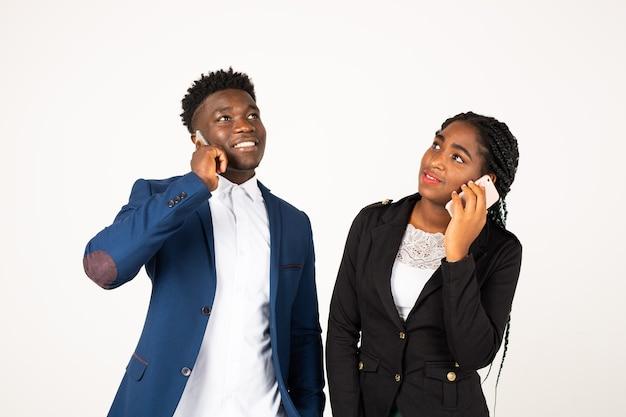 Красивые молодые африканцы на белом фоне с телефонами в руках