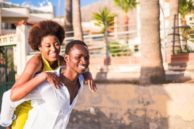 美しい若いアフリカのレースのカップルは、休暇の夏の日に一緒に楽しんで楽しんでいます。黒人男性と女性のための愛と友情のある幸せなライフスタイル。男は女を背負っている