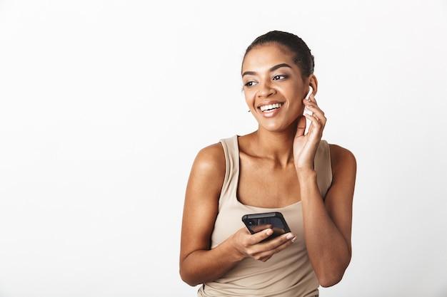 美しい若いアフリカの女性は、携帯電話を使用して、ワイヤレスイヤホンを身に着けている、白で隔離された立っているカジュアルな服を着ています