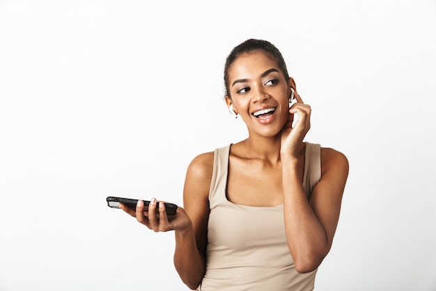 아름 다운 젊은 아프리카 여자 부담없이 흰색에 고립 된 서 입고, 무선 이어폰을 착용, 휴대 전화를 사용 하여