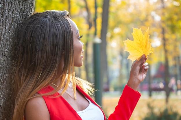 Красивая молодая африканская женщина собирает осенние листья в парке
