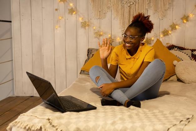 ベッドの上で自宅で宿題をしている美しい若いアフリカの女性