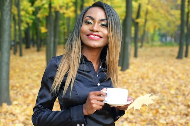 Красивая молодая африканская женщина пьет кофе из белой чашки в осеннем парке