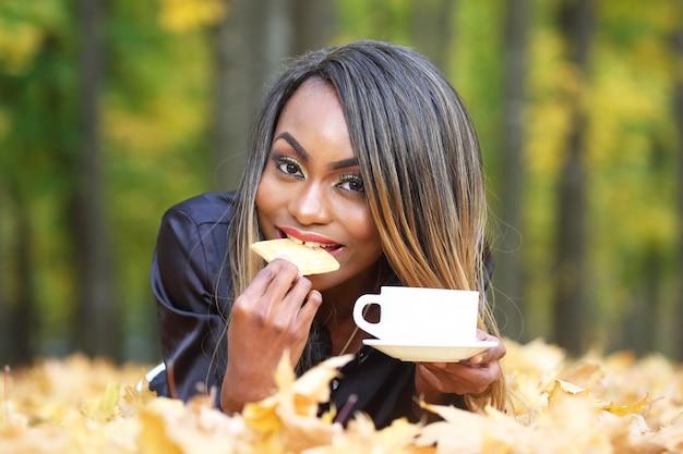 Красивая молодая африканская женщина ест печенье и пьет кофе из белой чашки на осенних листьях в парке