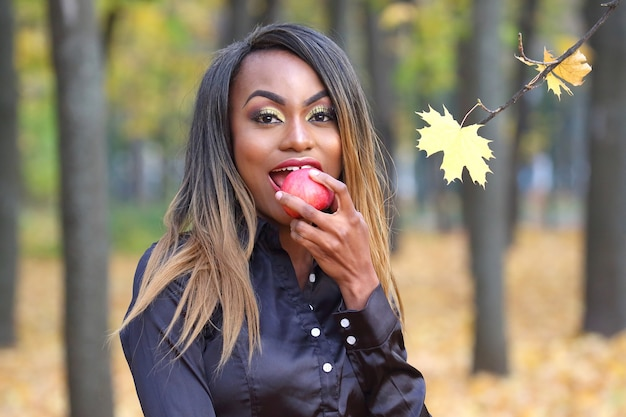 Красивая молодая африканская женщина ест красное яблоко на осенних листьях в парке
