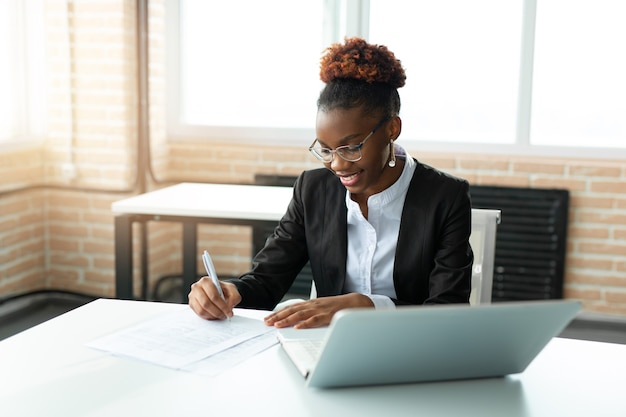 Beautiful young african woman in glasses with laptop