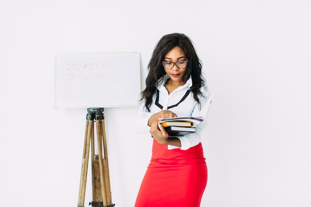 Beautiful young african woman holding documents and books, standing near the board