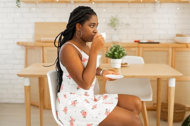 お茶を飲む台所で夏のドレスを着た美しい若いアフリカの女性