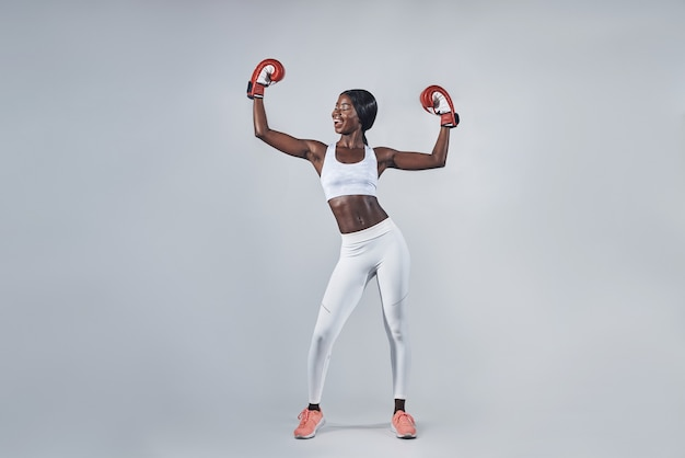 腕を上げたままボクシンググローブで美しい若いアフリカの女性