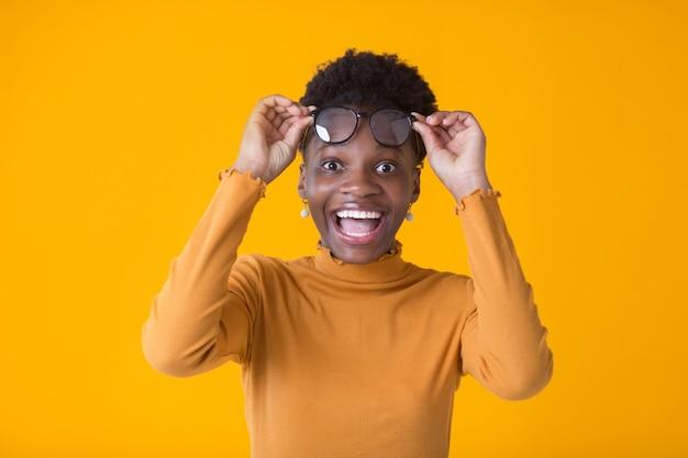 黄色の背景にガラスの美しい若いアフリカ人女性