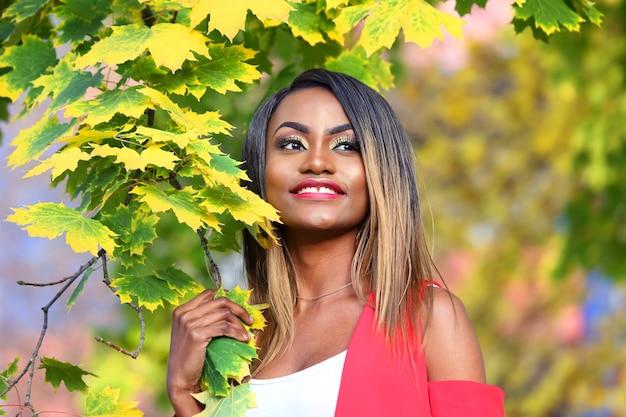 Красивая молодая африканская женщина в красном на осенних листьях