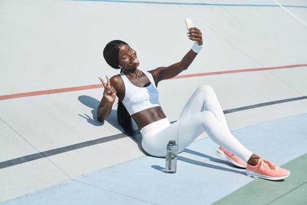 ビデオ通話と笑顔のスポーツ服を着た美しい若いアフリカの女性
