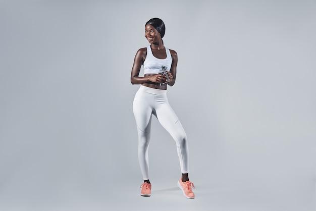 물병을 들고 웃고 있는 스포츠 의류를 입은 아름다운 젊은 아프리카 여성
