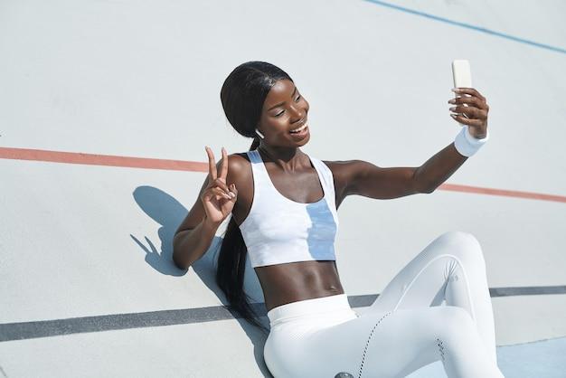 自撮りと笑顔を作るスポーツ服の美しい若いアフリカの女性