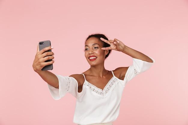 핑크 backgroung 벽에 고립 된 아름 다운 젊은 아프리카 여자 휴대 전화로 selfie를 받아